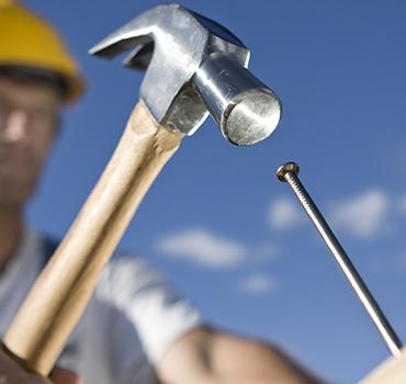 Tømrer som er ved at slå et søm i
